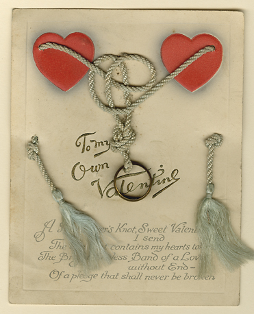"To My Own Valentine. Published by B.B., London and New York. Printed in England.  This Valentine features a brass ring tied up in the string of a tassel. At the bottom of the card is a poem and at the top embossed hearts. Written on verso ""Feb 14 1914"" with the name of who sent and received the card. Image size 6 x 4 3/4 inches. LINK."